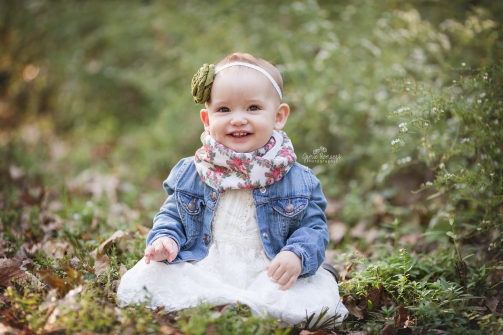 little girl sitting next to wildflowers, 1 year old