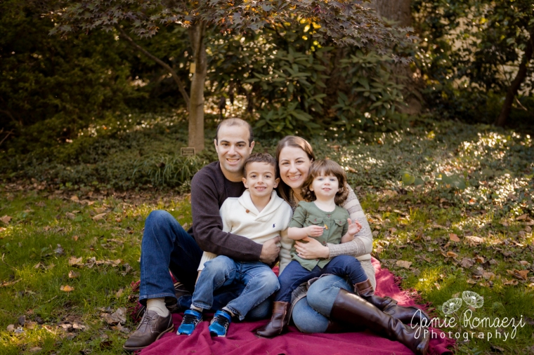 Family photo at McCrillis Gardens. Family sitting on maroon blanket in front of trees.