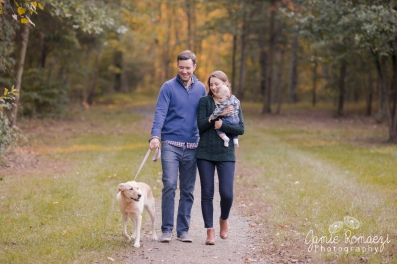 Family walking on trail in the fall with dog and baby.