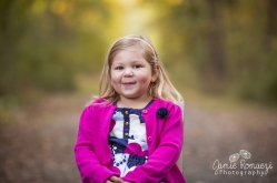 Blonde hair, brown eyed little girl with dimples wearing a pink cardigan over pattern dress.