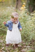 little girl walking next to wildflowers, 1 year old