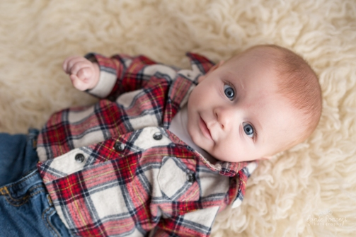 3 month old baby photos in studio wearing a red plaid shirt and laying on a flokati