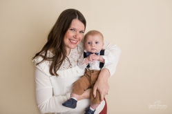 3 month old baby photos in studio with his mom on savage bone seamless paper, wearing suspenders and a bow tie