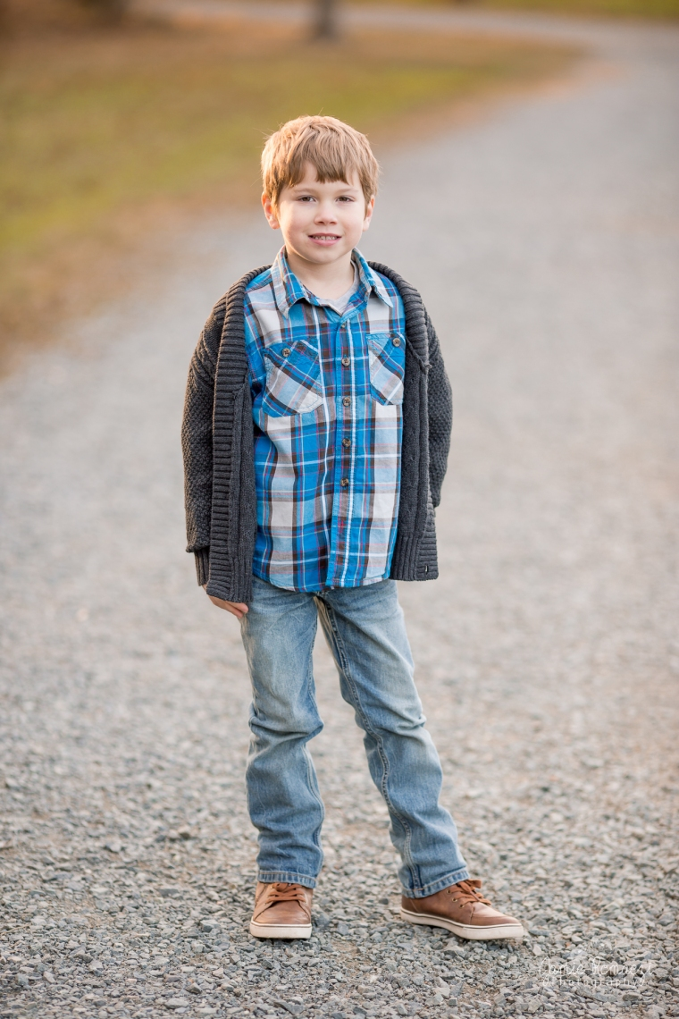 6 year old boy in blue plaid with gray sweater standing on a trail to have his photo taken