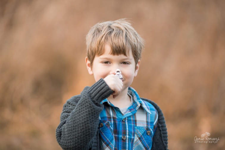 6 year old boy in blue plaid with gray sweater holding a stormtrooper lego man