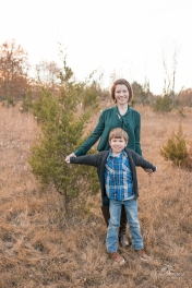 6 year old boy in blue plaid and gray sweater with mom in green in front of a small pine tree for christmas photos