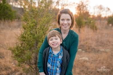 6 year old boy in blue plaid and gray sweater with mom in green in front of a small evergreen tree for christmas photos