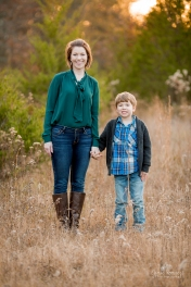 6 year old boy holding his mom's hand for family portraits