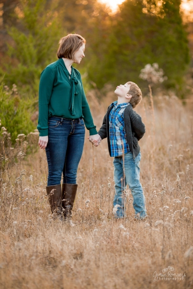 6 year old boy holding his mom's hand and blowing her a kissstanding in a field of grass