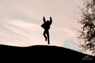 silhouette photo of child jumping at sunset