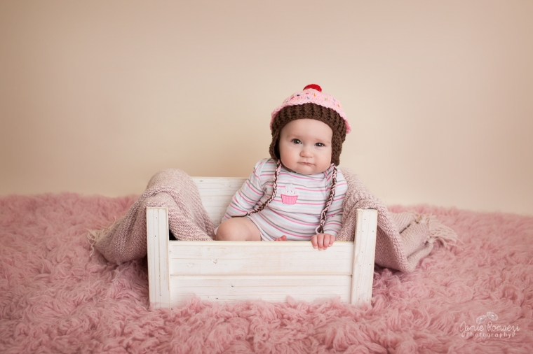 6 month old baby sitting in a prop wearing a cupcake hat