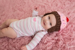 6 month old laying down wearing cupcake hat