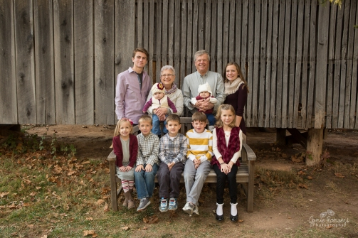 Extended family photos with grandparents, picture of cousins in front of a barn. Grandparents are holding the youngest cousins.