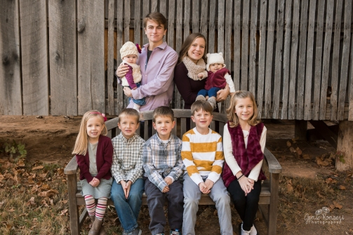 Extended family photos, picture of cousins in front of a barn. Oldest cousins are holding the youngest cousins.
