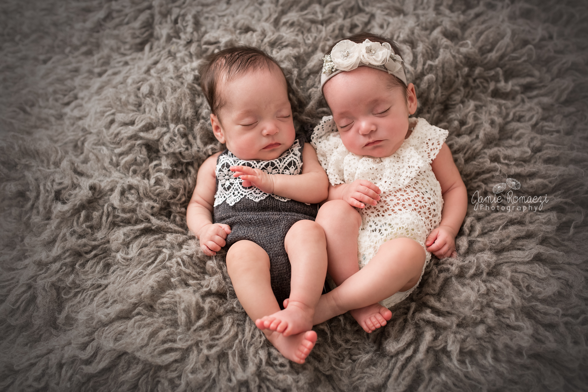 Micro preemie, newborn twin session. Identical twin girls on gray backdrop in gray and white outfits.