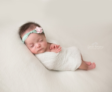 Micro preemie, newborn twin session. Baby wrapped in white on white backdrop with mint and pink headband.