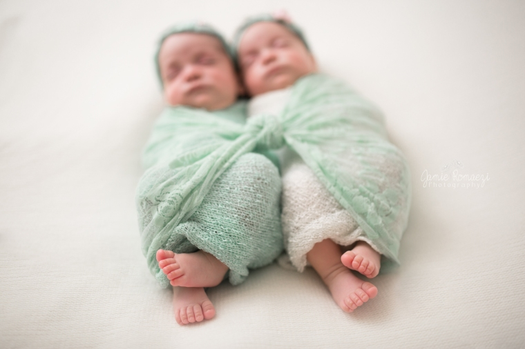 Micro preemie, newborn twin session. Identical twin girls wrapped in mint and white on white backdrop with mint and pink headbands.