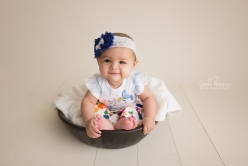 6 month old baby sitting in bowl with blue and floral pants.