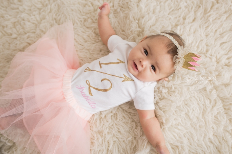 6 month old baby laying on rug wearing pink and gold custom 1/2 (half) birthday outfit.
