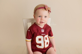 Baby sitting in chair wearing a redskin jersey and matching bow.