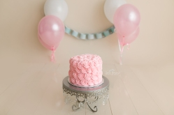 Pink cake on a cake stand with balloons