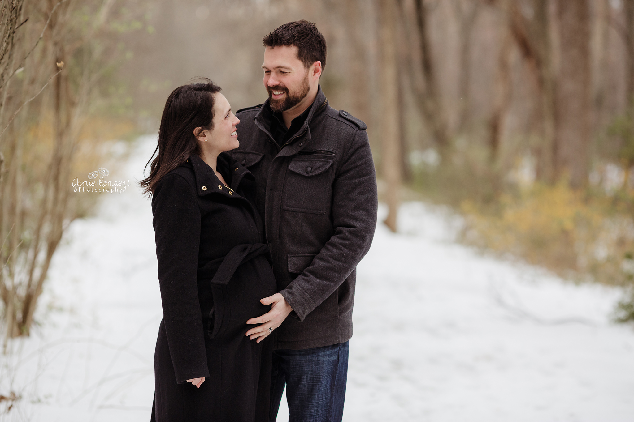 Couple wearing coats in snow maternity photos