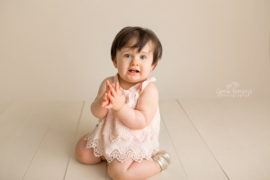 1 Year old looking at camera clapping.