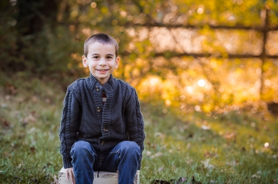 Boy in a gray sweater smiling for the camera.