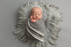 Newborn baby boy photos done in grays and neutrals, wearing bonnets/hats and wrapped/swaddled