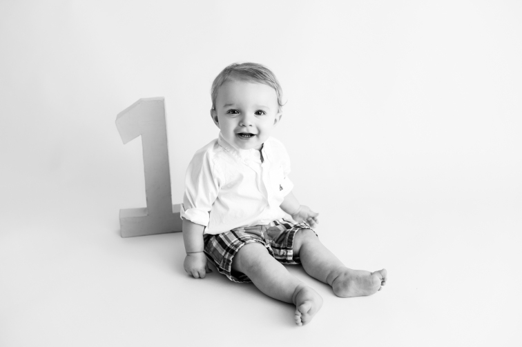 Black and white image with baby boy grinning with the number 1 behind him.