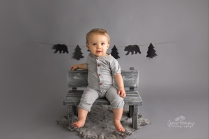 One year old sitting on a toddler bench wearing a gray romper in front of a wilderness themed banner.