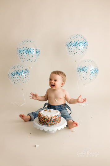 happy baby smashing his cake with sprinkles.
