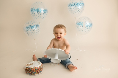 baby holding cake stand after he dumped the cake off of it.